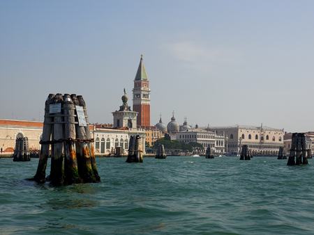 Wooden poles marking the channel in the lagoon in St Marks Basin, Venice, Italy with the Campanile and Doges Palace behind Editorial