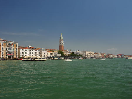 Cityscape of San Marco, Venice, Italy from the lagoon and St Marks Basin with a vaporetto waterbus ferry, Campanile and Doges Palace on the skyline