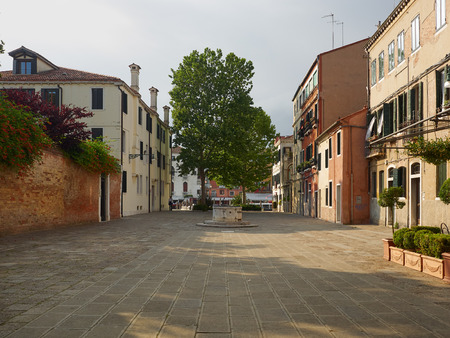 Open residential square with houses, ancient medieval well head and leafy green tree, Venice, Veneto, Italy