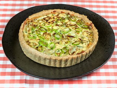 Homemade zucchini, leek and ricotta quiche set on a dark plate, on a red tablecloth Stock Photo