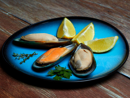 Fresh mussels and quartered lemons set on a blue plate, placed on a dark brown wooden surface Stock Photo