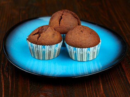 Home baked cocoa muffins set on a bright blue plate, placed on a dark brown wood board