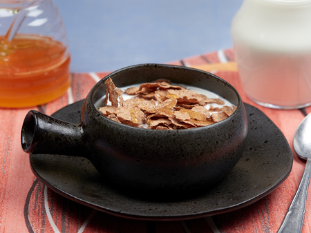 A bowl of oat bran flakes with milk and honey set on a red napkin, on a blue tablecloth, with a jar of honet and a jug of milk Stock Photo