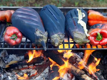 Roasting eggplants and red peppers over a campfire