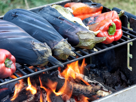 Eggplants and red peppers baking on the roast outdoors