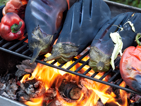 Roasting eggplants and red peppers on a grill over an open fire