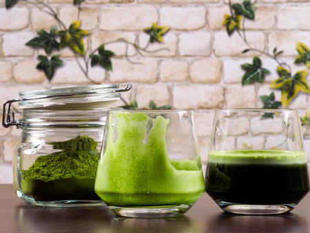 Two glasses of green juice, one full and one empty, plus one jar of green juice powder, set over a wenge board, with a background of brick wall and ivy leafs