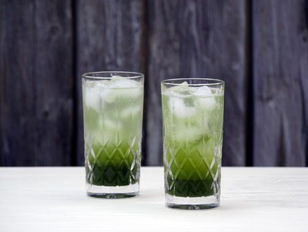 Two crystal glasses filled with layered matcha soda, with homemade matcha syrup, ice cubes and carbonated water