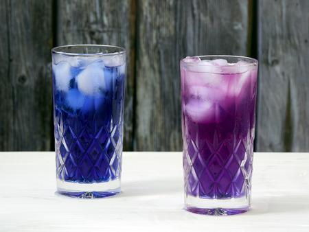 Adding lemon juice to butterfly pea flower (Clitoria ternatea) ice tea turns its color to a vibrant magenta. Stock Photo