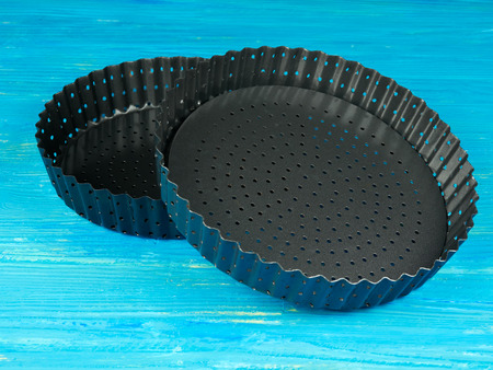 Empty tart or pie trays, set on a blue wooden board