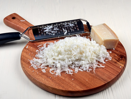 A heap of freshly grated parmesan, on a wooden board, and a special parmesan grater