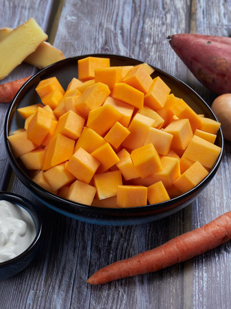Ingredients for butternut squash soup with sweet potatoes and gingerl, on gray rustic background