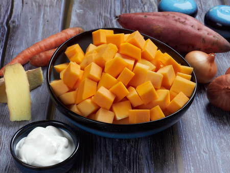 Ingredients for butternut squash soup with sweet potatoes and ginger, on gray rustic background