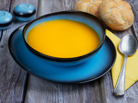 Butternut squash soup served in a blue bowl, on gray rustic background Stock Photo