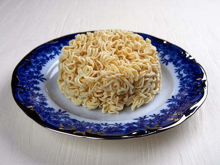 Block of uncooked instant noodles, on a blue plate set on a white wooden board