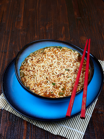 Shin Ramyun noodles, prepared, in a blue bowl set on a brown wooden board, with red chopsticks