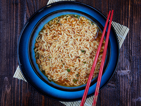 Shin Ramyun noodles, prepared, in a blue bowl set on a brown wooden board, with red chopsticks, top view Archivio Fotografico