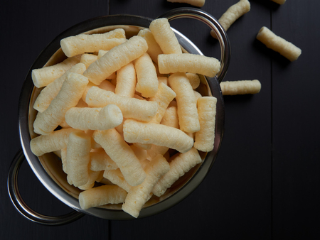 Crunchy, salty corn puffs snacks, also known in Romanian as pufuleti, in a red strainer, on dark brown background Stock Photo