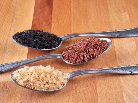 Uncooked black, red and integral rice on silver spoons, on a rustic wooden board Imagens