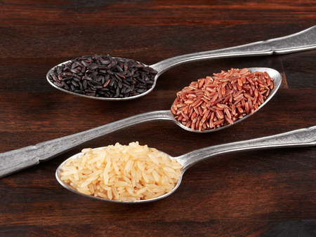 Uncooked black, red and integral rice in olive wood bowls, on a rustic wooden board