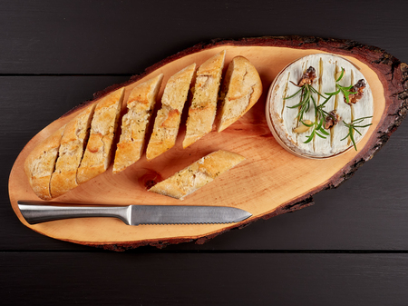 Baked Camembert with walnuts, rosemary stalks and garlic cloves, served with crusty garlic gread, on a rustic board, flat lay Stock Photo