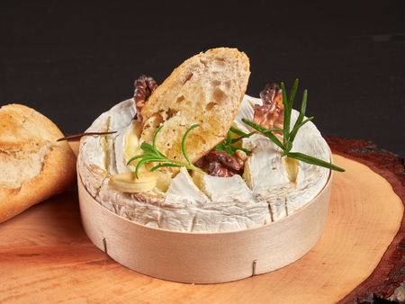 Baked Camembert with walnuts, rosemary stalks and garlic cloves, served with crusty garlic gread, on a rustic board, close-up view