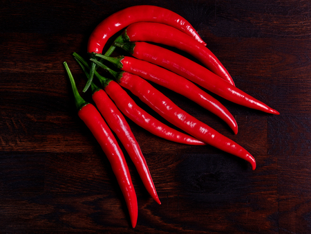 Red chilis on a dark rustic wooden oak board
