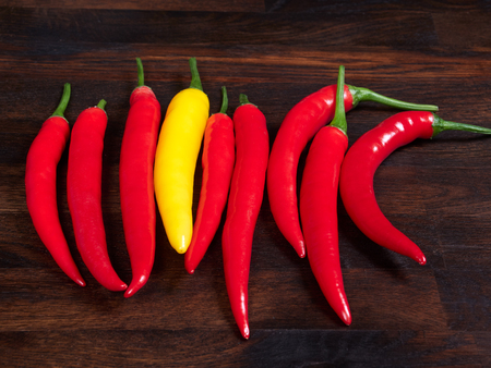 Red and yellow chilis on a dark rustic wooden oak board