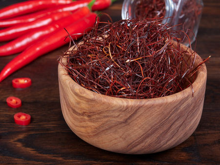 An olive wood bowl filled with thin threads of sun-dried red chili also known as angel hair chili, having a mild heat and fruity, full flavor
