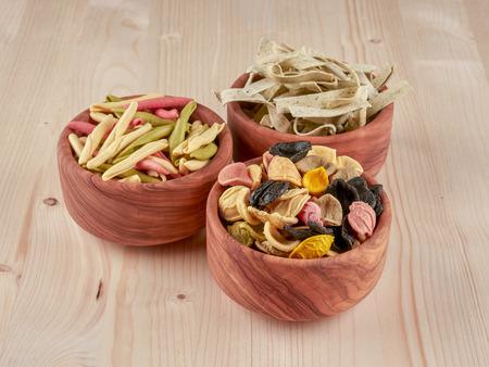 Three olive wood bowls with uncooked, colorful orechiette, fusilli and tagliatelle pasta