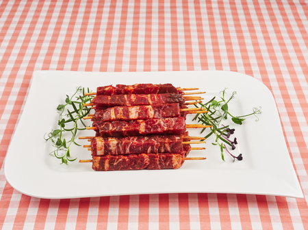 Raw fresh beef and lamb skewers, uncooked, on a white plate, garnished with fresh pea shoots and rosemary sprigs