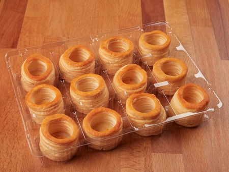 A tray of ready-made small puff pastry shells, on a wooden board Stock Photo