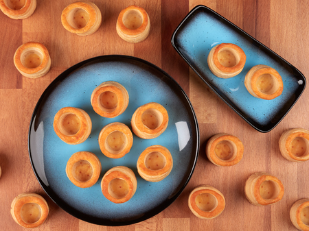 Ready-made small puff pastry shells, on a wooden board Stock Photo
