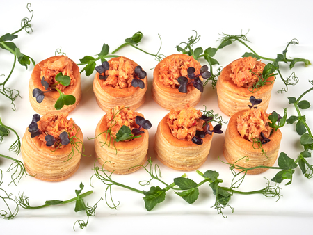 Puff pastries with a spicy, chunky salmon filling, garnished with pea shoots