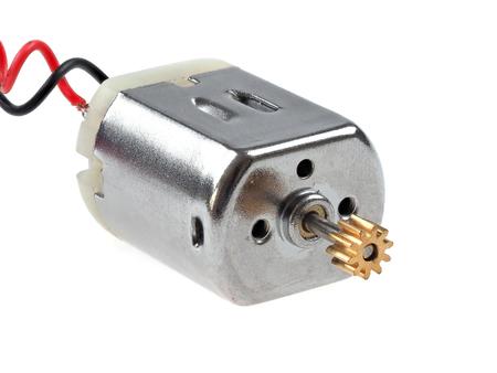 Mały silnik prądu stałego, z przewodami czerwonymi i czarnymi, na białym tle. Rodzaj silnika stosowany w wielu projektach elektronicznych i studenckich.
