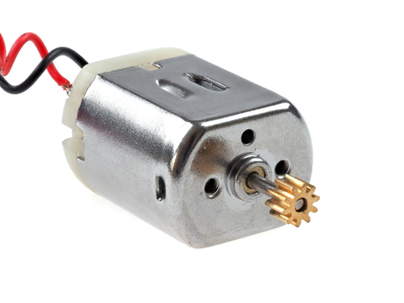 Small size direct current motor, with red and black wires, isolated on white. The kind of motor used in many electronics and student projects. Foto de archivo