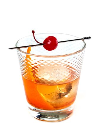 Old fashioned cocktail decorated with a slice of orange zest and a cocktail cherry, on white background      Zdjęcie Seryjne