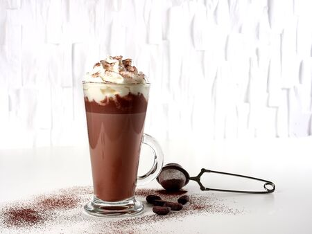 Hot chocolate latte with whipped cream, in tall glass, sprinked with cocoa powder, on white background Stok Fotoğraf