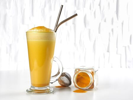Honey sweetened turmeric latte, in a tall glass, with metal straws, on white background