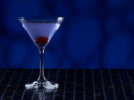 Aviation cocktail on blue background, copy space on the right side