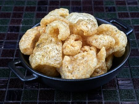 Pork rinds also known as chicharron or chicharrons, deep fried pork skin. Savory snack.