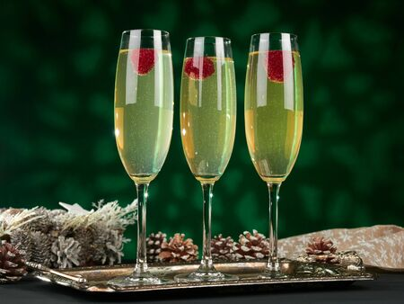 Three glasses of limoncello prosecco cocktail, garnished with a fresh raspberry, on a green background