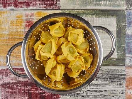 Fresh Italian traditional Tortelloni pasta with basil filling, uncooked, in a colander Stock Photo