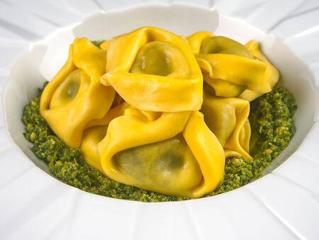 Fresh Italian traditional tortelloni with pesto sauce, on an elegant white plate