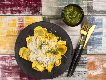 Fresh Italian traditional tortelloni with pesto sauce, on a rustic plate, with extra pesto Stock Photo