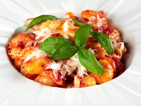 Oven baked gnocchi alla sorrentina, with tomato sauce, mozzarella and green fresh basil Foto de archivo