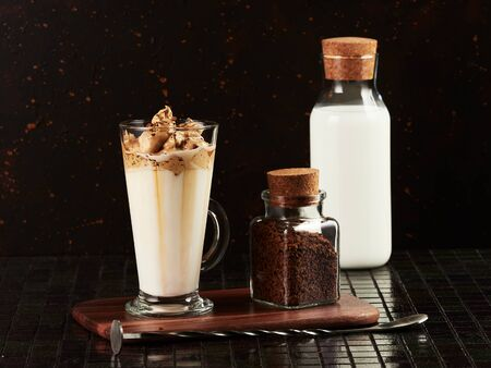 Dalgona Coffee: a layered drink made of hot milk and whipped instant coffee, on dark brown background