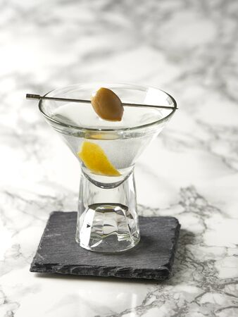 Classic Martini cocktail decorated with an with olive and lemon peel, on a marble background