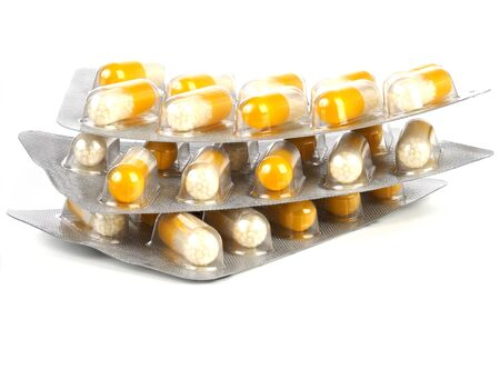 Yellow and white pills or capsules in blisters, isolated on white background 免版税图像