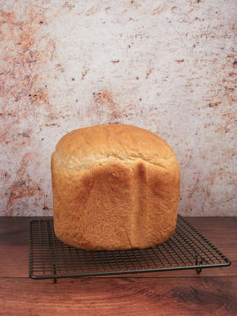 Fresh bread made at home with the bread machine, set on a gray cooling rack, on brown background 免版税图像 - 152390983